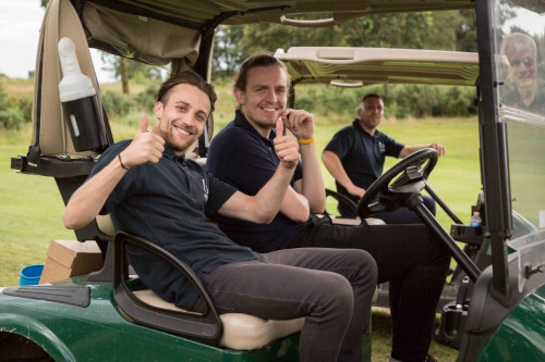 men giving thumbs up whilst sat in a golf caddy
