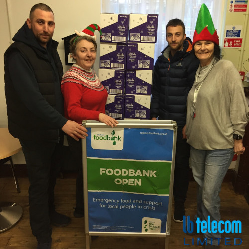 a group dressed in Christmas attire stood around a foodbank sign